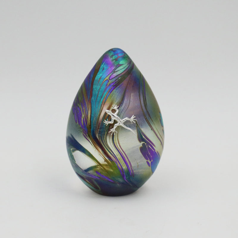 Handmade glass goose egg shaped paperweight in iridescent purples blue and clear with a climbing silver gecko