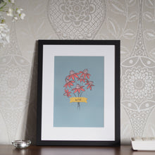 Load image into Gallery viewer, A print of a posy of pink flowers on a pale teal background, with a golden yellow banner saying wild. The print is mounted and framed in a black frame, and is sat atop a wooden sideboard. This is placed in front of ornately patterned wallpaper, and has two candles on the top, as well as a glimpse of white flowers in the top left corner.