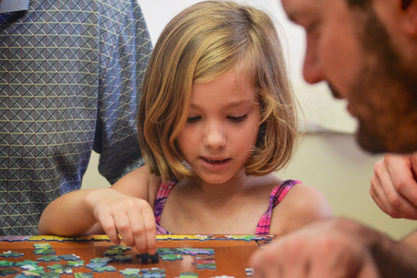 Father and daughter building puzzle together