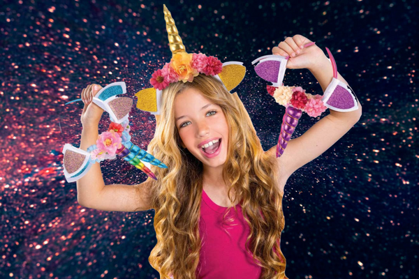 Young girl holding DIY Unicorn Headbands in front of a space themed background
