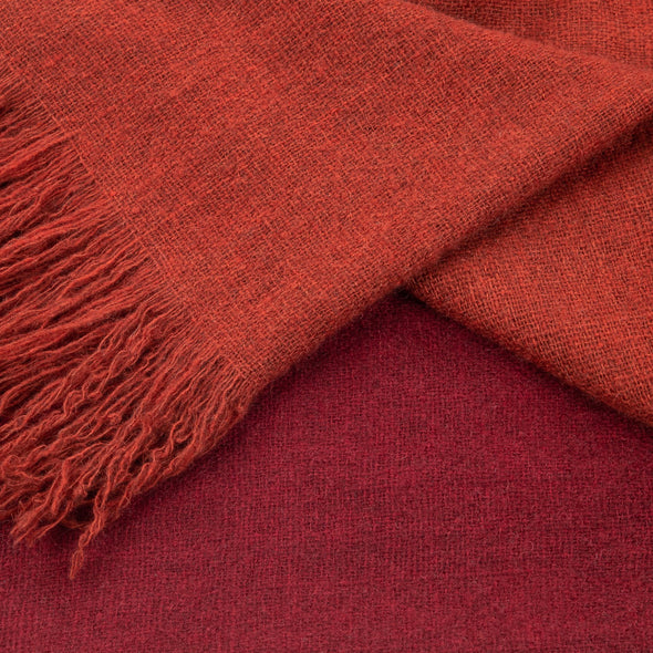 Folded detail of scarf which has been dip dyed in subtle shades of rust to dark red crimson. Made from wool, yak and cashmere, a soft and luxurious scarf from Thread Tales company
