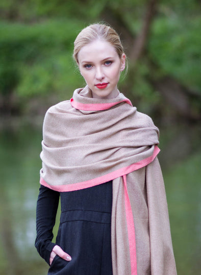 Model wearing scarf in camel beige blended with cream scarf with light pink stripe 2cm wide down both edges. As featured in The Sunday Times luxurious scarf from Thread Tales company