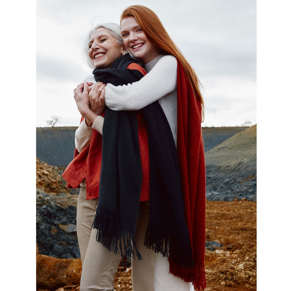 Two models, wearing scarves which have been dip dyed in subtle shades. One is dark grey to almost black and the other is rust to a deep crimson. Made from wool, yak and cashmere, these are a soft and luxurious scarf from Thread Tales company