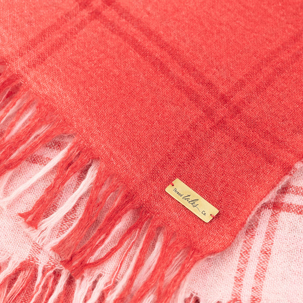 Folded detail of blush pink scarf woven with subtle open check in darker shade then dip dyed in shades of red to subtle effect. Made from wool and cashmere lightweight warm luxurious scarf from Thread Tales company