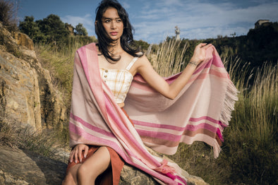Model wearing cashmere stripe scarf in shades of cream, tan, pink, coral. Handwoven and sustainably made from eco dyes by Thread Tales