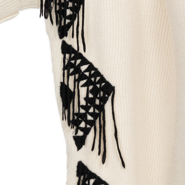Close up of embroidered edge of one size poncho loose-fitting wrap with sleeves knitted in cream 50% cashmere/wool mix edged with a hand-embroidered geometric design in charcoal grey black with trailing threads along edge of body and sleeves from Thread Tales company