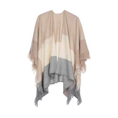 Model wearing cape in neutral tones of cream, beige and soft blue wide stripes in cashmere and wool handwoven finished with fringe from Thread Tales company