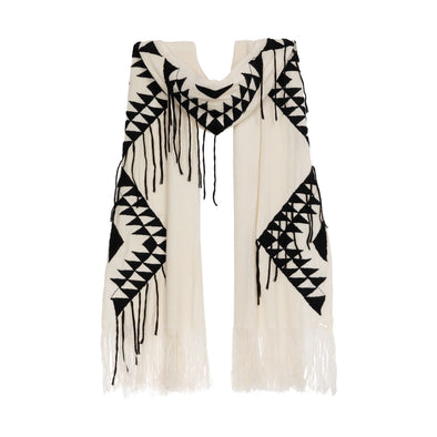 Model wearing large scarf wrap knitted in cream 50% cashmere and wool edged with a hand-embroidered geometric design in charcoal grey black with trailing threads along edge of pattern and long dramatic fringe from Thread Tales company