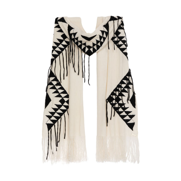 Hanging detail of large scarf wrap knitted in cream 50% cashmere and wool edged with a hand-embroidered geometric design in charcoal grey black with trailing threads along edge of pattern and long cream fringe from Thread Tales company
