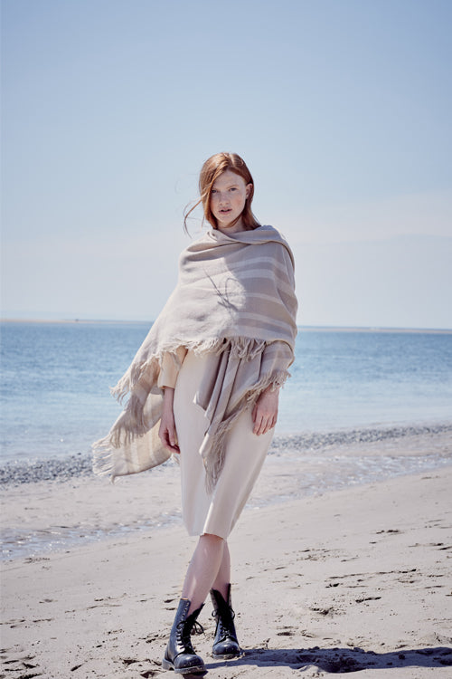 Model wearing fringed travel wrap light brown beige cream striped edge fringed cashmere wool from Thread Tales company