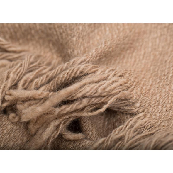 Folded fringe detail of 100% camel wool luxurious oversized blanket wrap in camel colour with cream selvedge edge stripe. Soft and thick this cosy travel wrap is from Thread Tales company