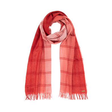 Model wearing scarf blush pink woven with subtle open check in darker shade then dip dyed in shades of red to subtle effect. Made from wool and cashmere lightweight warm luxurious scarf from Thread Tales company