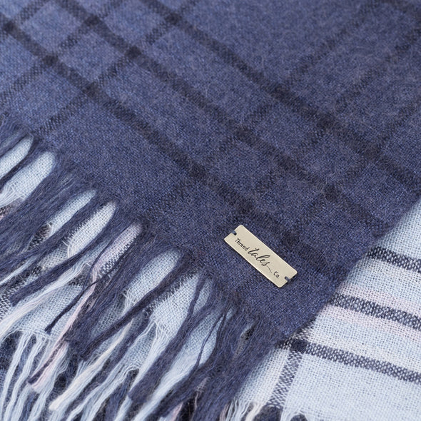 Folded detail of blue scarf woven with subtle open check in darker shade then dip dyed in shades of blue to subtle effect. Made from wool and cashmere lightweight warm luxurious scarf from Thread Tales company