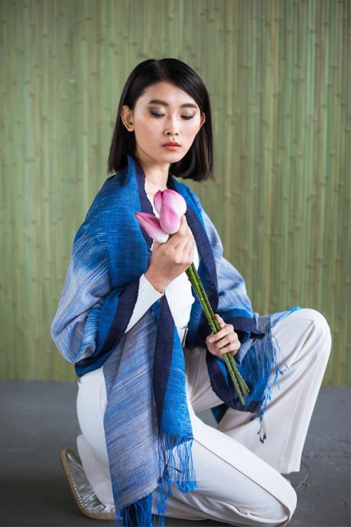 Model wearing Ikat blanket shawl blue light to dark azure shades lotus mandalay silk fabric handwoven to order from Thread Tales company