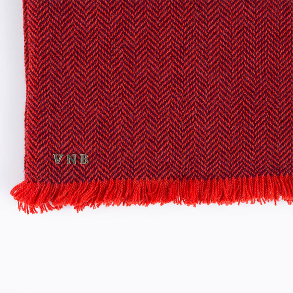 Folded detail of scarf in two tones of red herringbone weave in cashmere yak wool hand-finished with vibrant short fringe from Thread Tales company