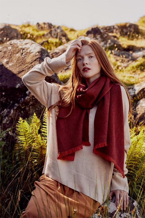 Model wearing red scarf in two tones of red herringbone weave hand-finished with vibrant short fringe from Thread Tales company