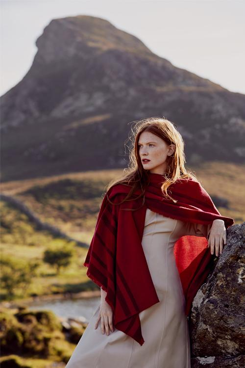 Model wearing fringed travel wrap red with crimson striped edge fringed cashmere wool from Thread Tales company