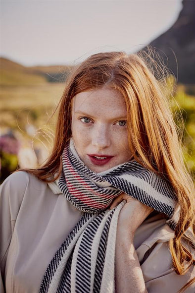 Model wearing scarf with red, black white twill stripes merino wool, handwoven heavyweight blanket from Thread Tales Company