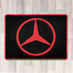 rectangular black and red rug with Mercedes logo in the middle