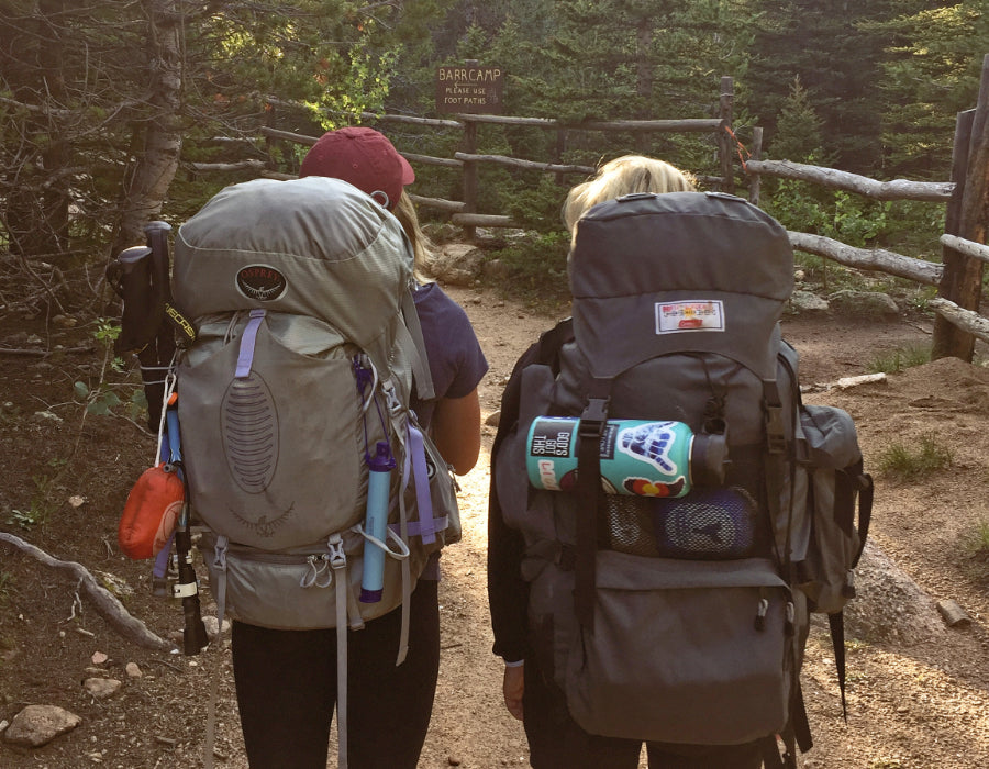 2 female backpackers headed up a wooded trail, both carrying large packs with camping items hanging from straps