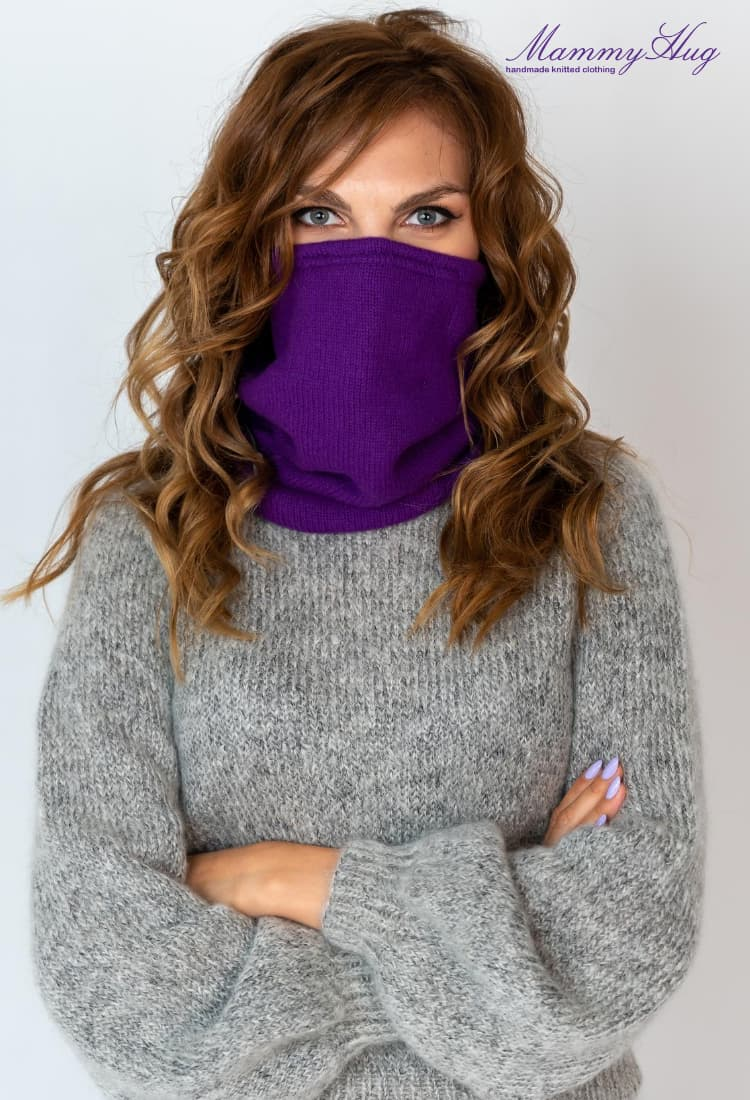 Girl in a woolen sweater covers her face with snood