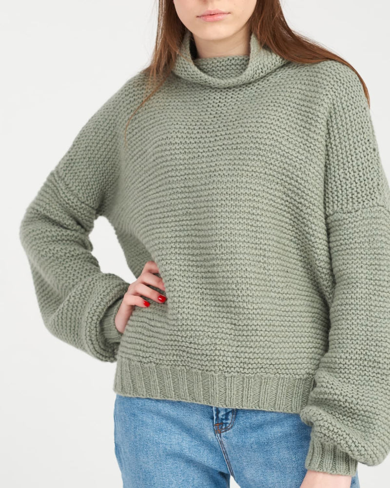 green cable knit sweater close-up