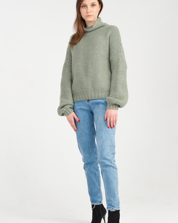 Woman in knitted winter sweater and blue jeans