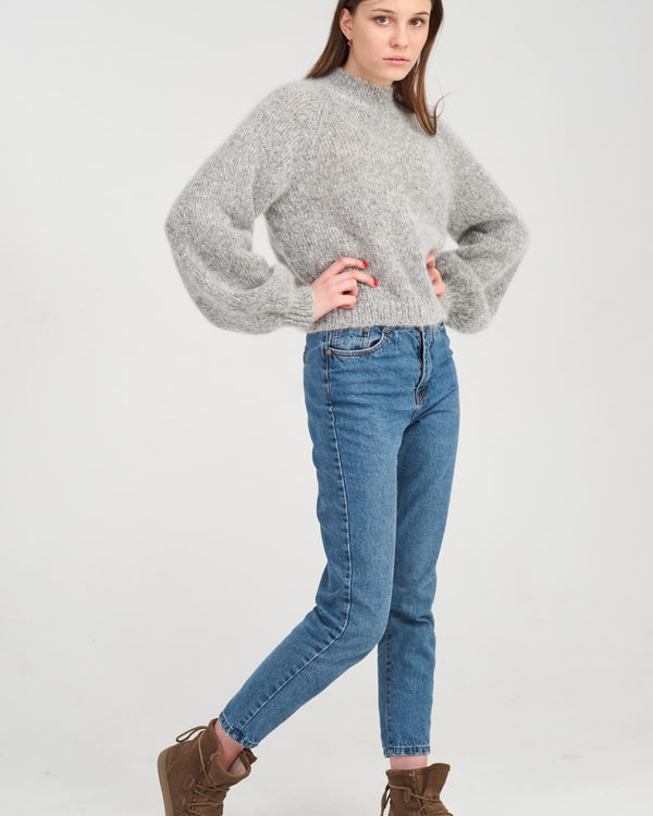 Young girl in a gray knitted sweater and jeans