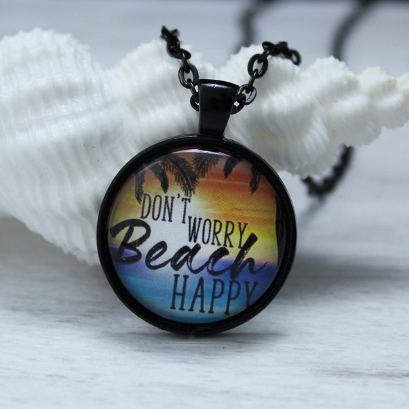 don't worry beach happy with ocean and sunset on black chain by favored whispers, cabochon