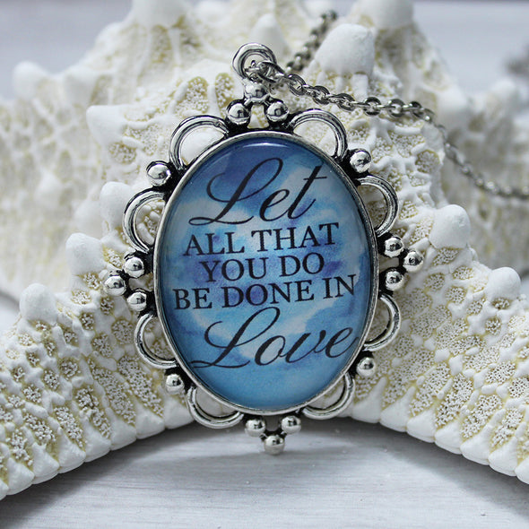 Let All You Do Be Done In Love, oval, opera length, 28 inches, blue background with heart, silver chain