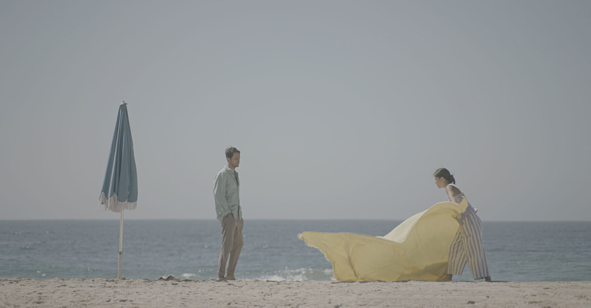 A man and woman setting a blanket on the beach.