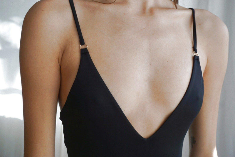 Detail view of women's sexy black bodysuit