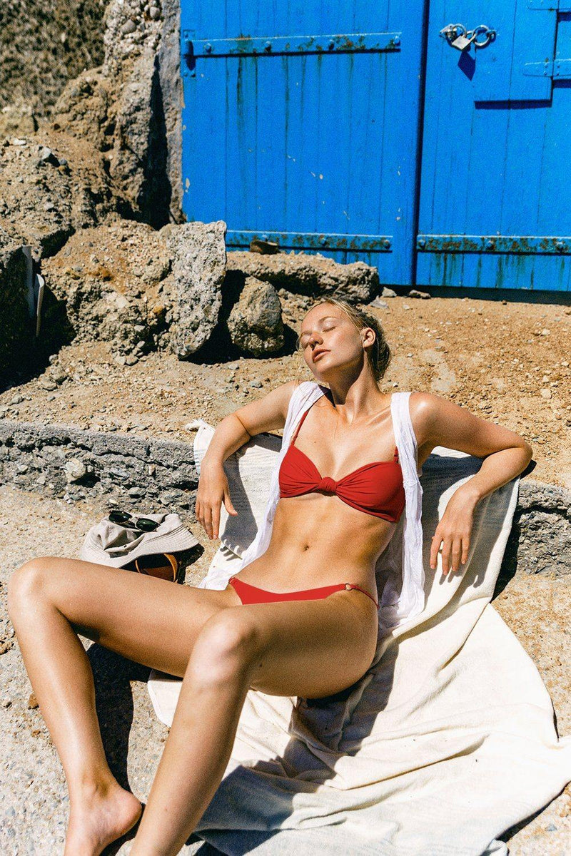 Model wearing red designer swimsuit