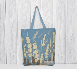 Colourful gift – Blue and Cream Meadow Sky tote bag with a blue handle hanging in front of bleached wooden panel.