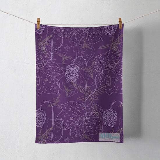 Colourful gift – Purple, White and Yellow Fritillaria flower design tea towel hanging from clothesline, shadows showing on off-white background.