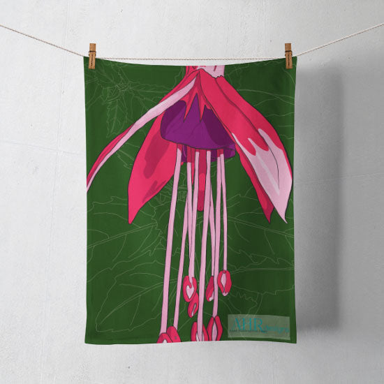 Colourful gift – Pink, Purple and Green Fuchsia flower design tea towel hanging from clothesline, shadows showing on off-white background.