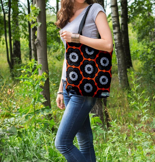 Patterned tote bag on woman's shoulder.