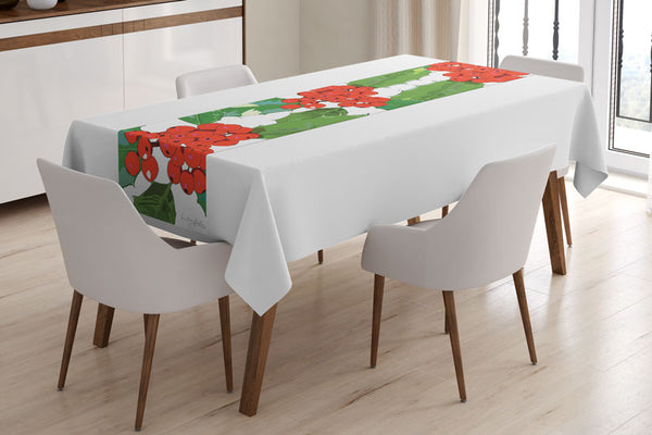 Holly table runner designed by Anne Harrington Rees, shown laid on a table with a white tablecloth underneath.  The design features red berries and spiny green leaves on a white background.