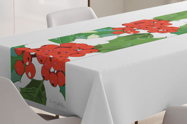 Close up of the Holly table runner designed by Anne Harrington Rees, shown laid on a table with a white tablecloth underneath.  The design features red berries and spiny green leaves on a white background.