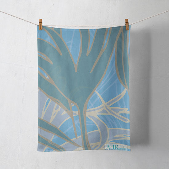 Colourful gift – Blue, Turquoise and Sand Kelp seaweed design tea towel hanging from clothesline, shadows showing on off-white background.