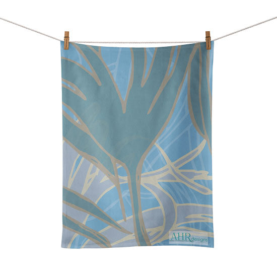 Colourful gift – Blue, Turquoise and Sand Kelp seaweed design tea towel hanging from clothesline, white background.