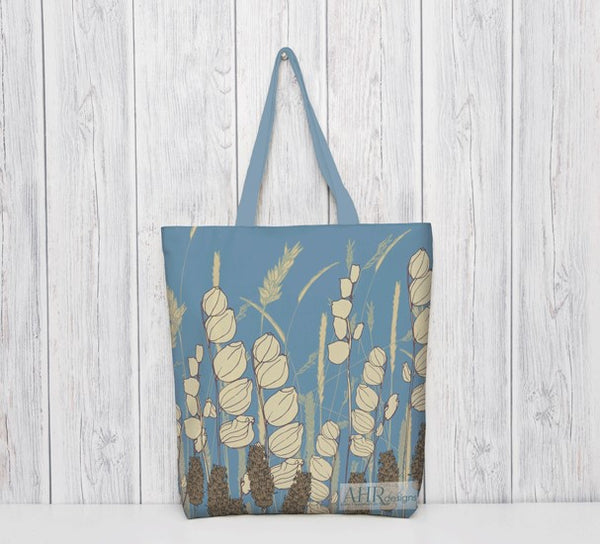 Colourful gift – Blue and Cream Meadow Sky tote bag with blue handle hanging in front of bleached wooden panel.