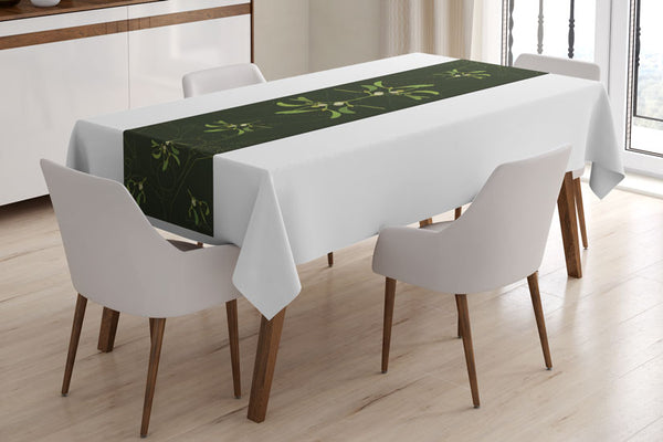 Mistletoe table runner designed by Anne Harrington Rees, viewed on a table covered with a white tablecloth.  Symmetrical design of leaves and berries on a dark green background.
