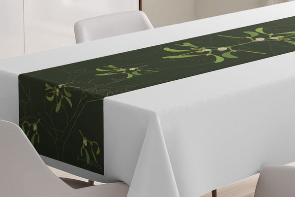 Close up of the Mistletoe table runner designed by Anne Harrington Rees, viewed on a table covered with a white tablecloth.  Symmetrical design of leaves and berries on a dark green background.