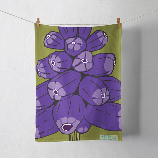Colourful gift – Purple and Green Muscari flower design tea towel hanging from clothesline, shadows showing on off-white background.
