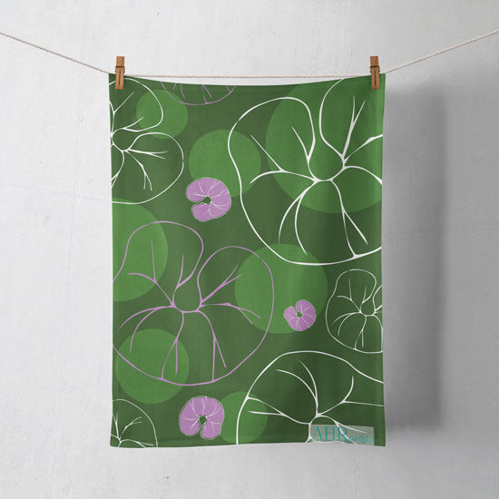 Colourful gift – Green, Pink and White Sea Bindweed flower design tea towel hanging from clothesline, shadows showing on off-white background.