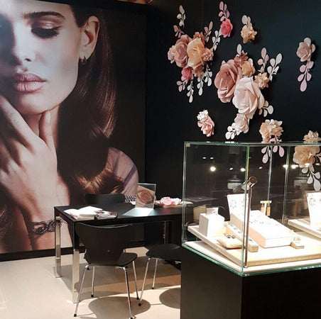 Exhibition stand for jewelry brand decorated with paper flowers