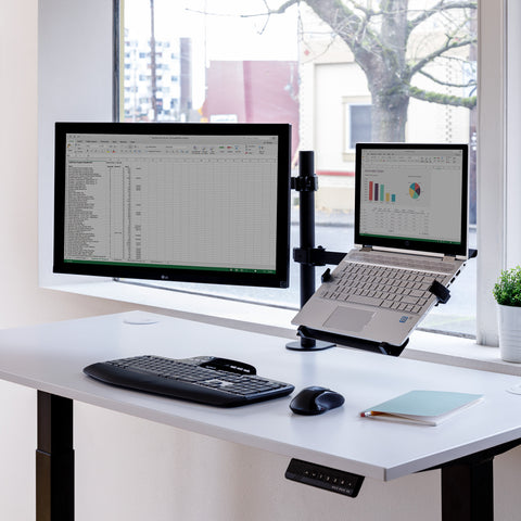 Black laptop and monitor mount on a electric powered stand up desk
