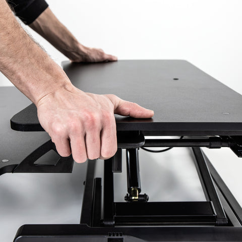 Black stand up desk topper being raised with the hand lever feature