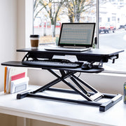 Black stand up desk topper in the office with a laptop and other desk accessories